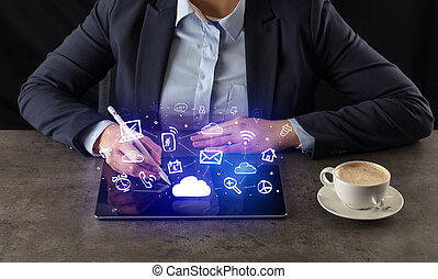 Business woman working on tablet with application symbols above