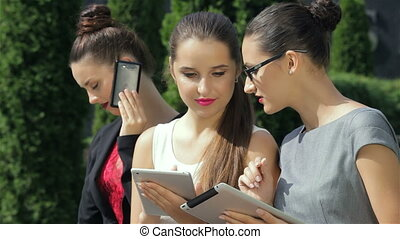 Business woman, working on the tablet, one of the girls looking at the camera