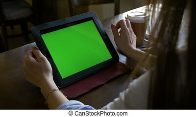 Business woman working using tablet pc with green screen and drinking coffee