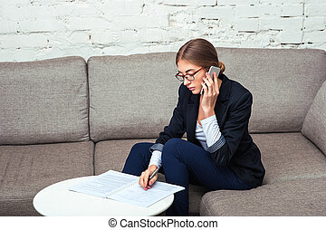 Business woman working with documents on sofa