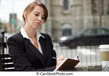 Business woman writing in her journal