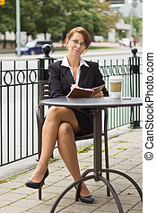 Business woman writing in journal at outdoor cafe