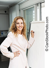 Business woman writing on flip chart - Smiling businesswoman...