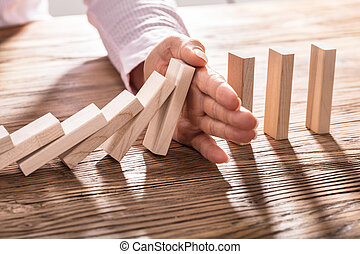Business Woman's Hand Stopping Falling Blocks On Table