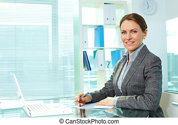 Cheerful business lady smiling at camera sitting at her workplace