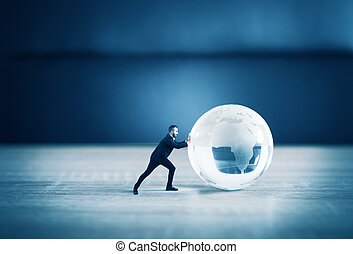 Businessman push a world glass sphere with continents on the table