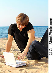 Business young guy working at laptop over beach
