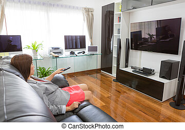 Business young woman watching TV in modern home office with comp