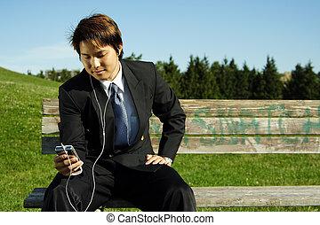 Businessman - A businessman listening to music