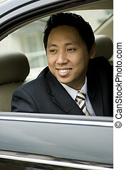 A young asian executive looking out of a car window