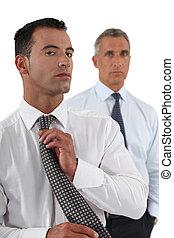 Businessman adjusting tie in front of colleague