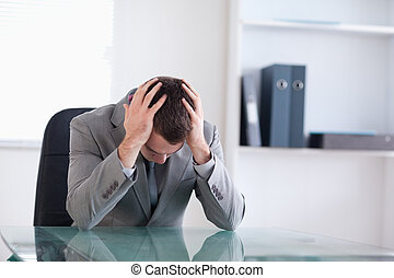 Businessman after failed negotiation sitting behind a table