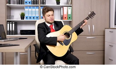 Businessman after long hours of work playing on acustic...
