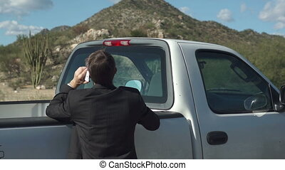 Annoyed businessman on the side of the road beside his truck facing away from the camera and talking on his cellular phone.