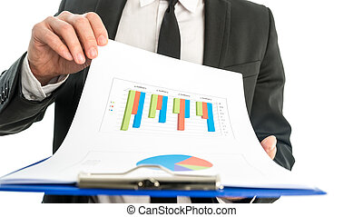 Businessman analysing a set of graphs and holding a map with sta