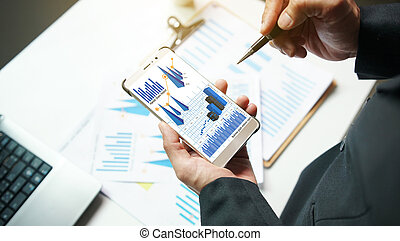 Businessman analysis charts and graphs showing on smartphone