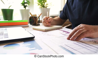Businessman analyzes financial report and writes notes in a notebook.