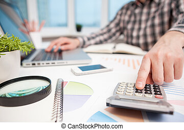 Businessman analyzing business graphs with magnifying glass