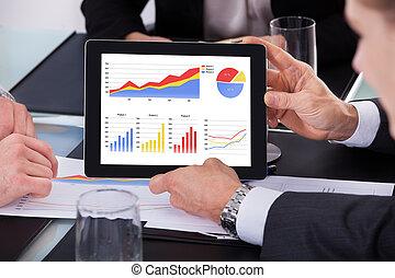 Businessman Holding Digital Tablet Over Graph Sitting At Desk