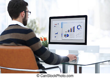 businessman analyzing graphs on computer at desk
