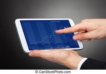 Businessman Analyzing Graphs On Digital Tablet