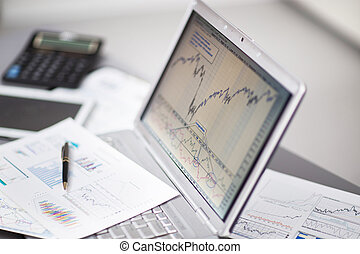 investment charts with laptop.
