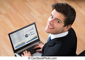 Businessman Analyzing Statistical Data On Laptop