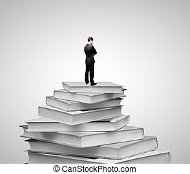 Businessman and books - Businessman standing on a pile of...
