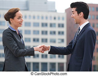 Businessman and business woman handshake outdoors