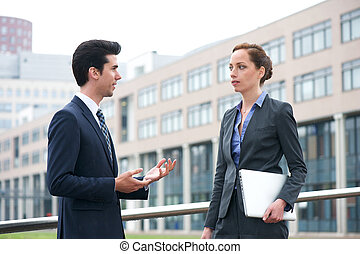 Businessman and business woman in discussion out of the office
