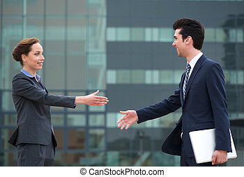 Businessman and business woman meeting with a handshake