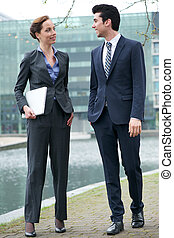 Businessman and business woman walking together outdoors