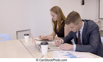 Businessman and businesswoman are working in co-working room...