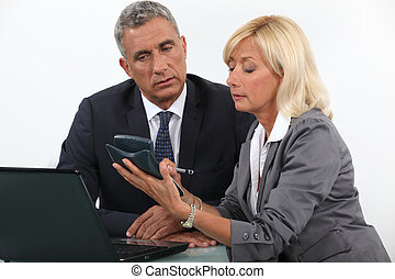 businessman and businesswoman calculating the budget