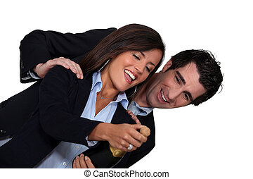 Businessman and businesswoman celebrating with bottle of champagne