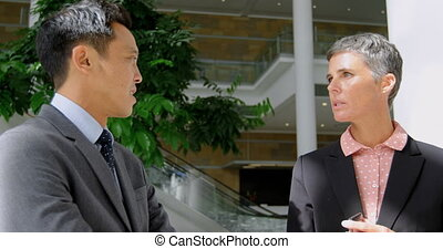 Businessman and businesswoman discussing in the office 4k