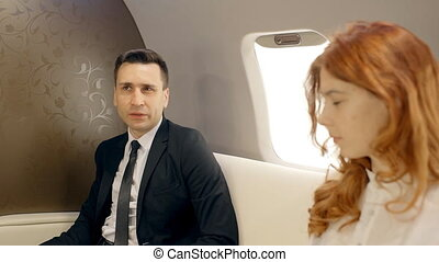 Businessman and businesswoman discussing their plans flying in private plane.