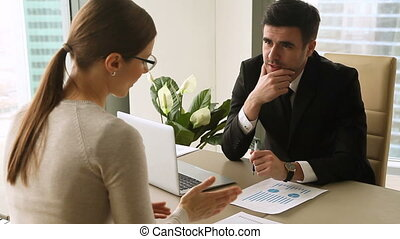 Businessman and businesswoman discussing project at meeting, giving high five