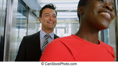 Businessman and businesswoman getting out of the elevator 4k...