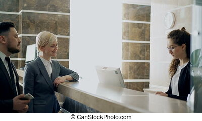 Businessman and businesswoman guests come to receptionist...