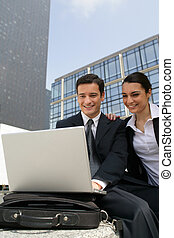 Businessman and businesswoman laughing in front of a laptop outdoors