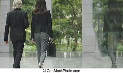 businessman and businesswoman leaving modern office building