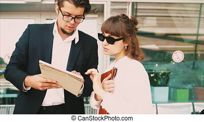 Businessman and businesswoman look at important papers ...