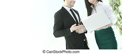 businessman and businesswoman looking at laptop while standing i