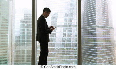 Businessman and businesswoman meeting near office window, woman is late