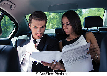 Businessman and businesswoman reading documents in car