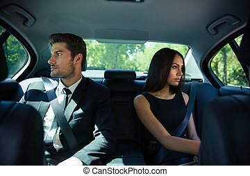 Businessman and businesswoman riding in car