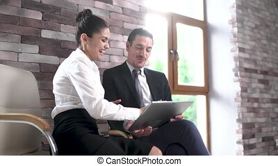 Businessman and businesswoman sit and have a discussion