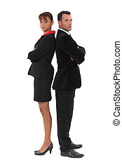 Businessman and businesswoman standing back-to-back