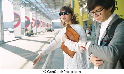 Businessman and businesswoman waiting for a taxi